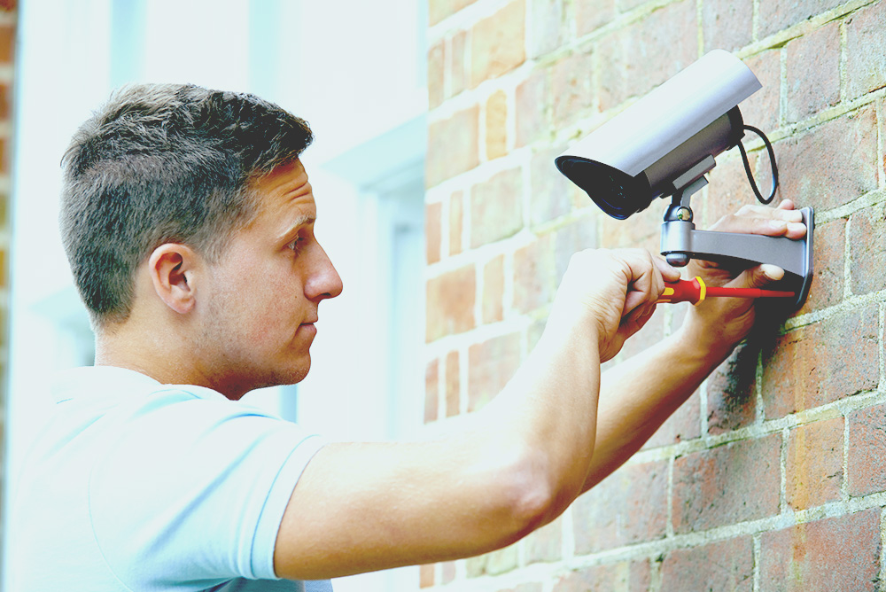 Security Consultant Fitting Security Camera To House Wall best solar powered security camera