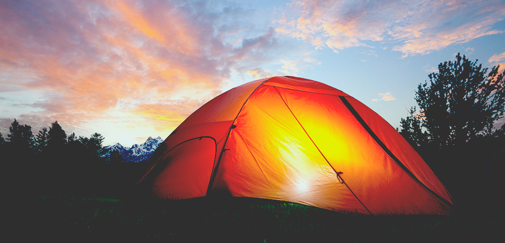 An orange tent with a light glowing inside at dusk near the Grand Teton mountains best portable solar panels