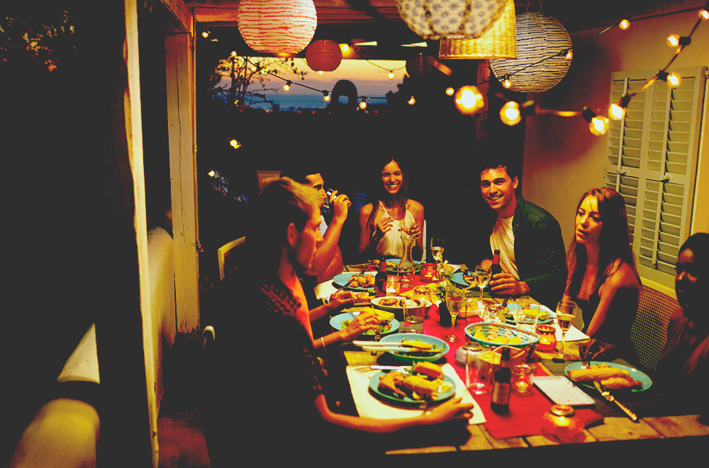 Friends eating and drinking at dinner party on a patio in evening with outdoor solar lights