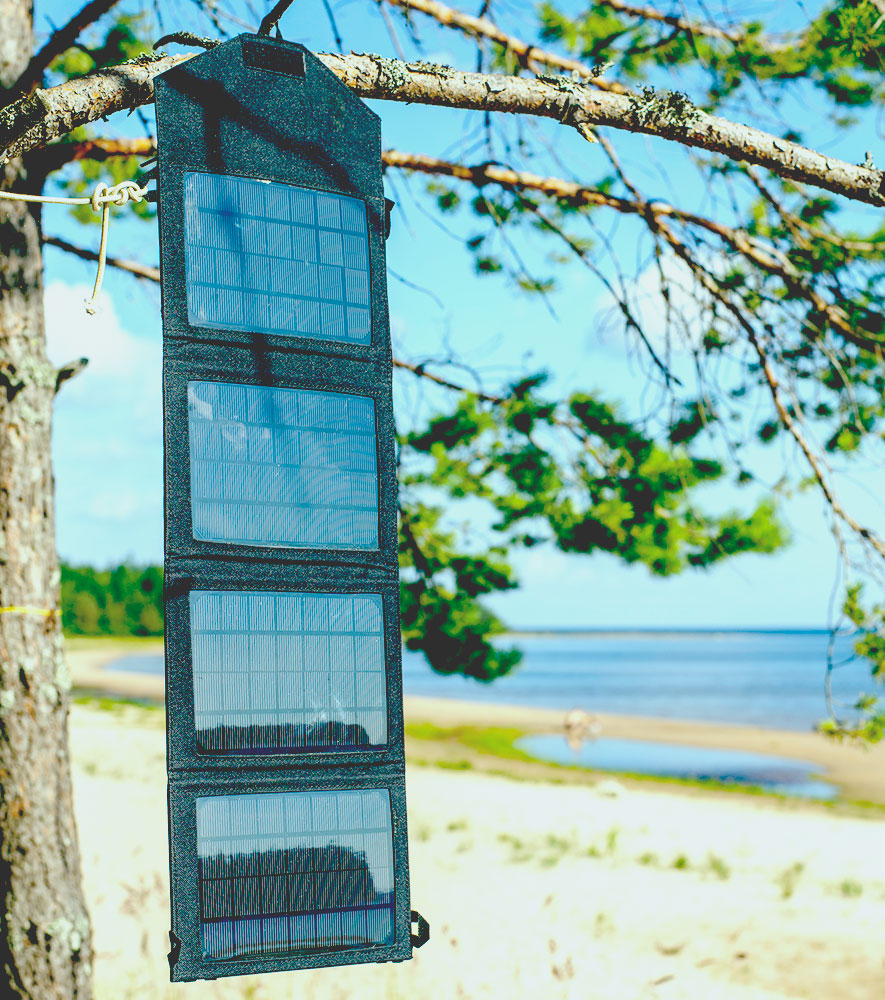 Portable foldable solar panel battery hanging on the outdoors on a pine tree