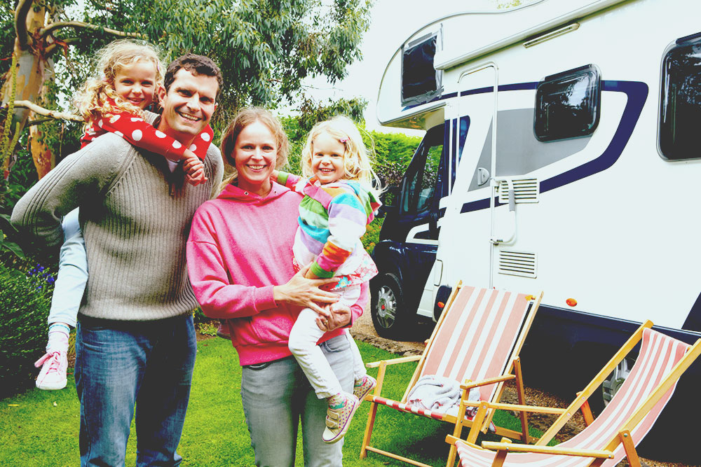 Portrait Of Family Enjoying Camping Holiday In Camper Van best portable solar panels
