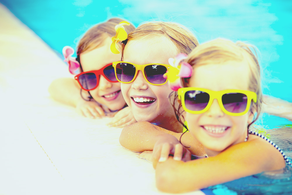 Happy children in the swimming pool. Funny kids playing outdoors. Summer vacation concept best solar pool heater