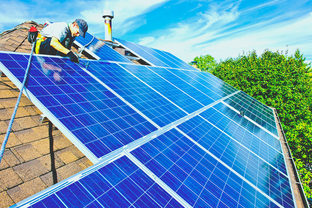 Man installing solar panels on a roof on a nice day web