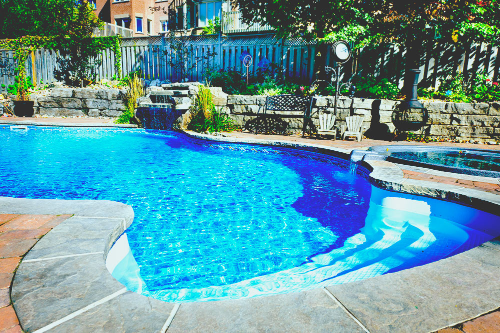 Residential inground swimming pool in backyard with waterfall and hot tub best solar pool heater