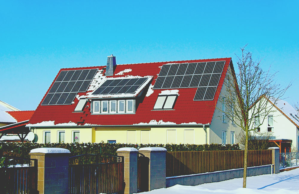 solar panels on building roof with snow web