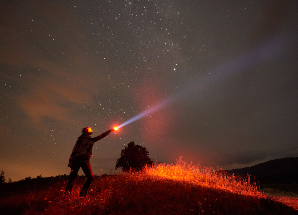 Silhouette of person standing against night starry sky in the mountains with a lamp in hand best solar flashlight
