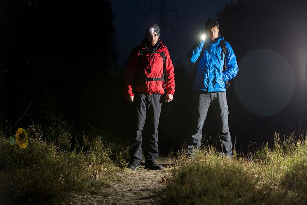 hikers standing in the dark with headlamp and flashlight best solar flashlight