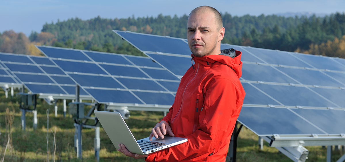 solar engineer with laptop in front of solar panels